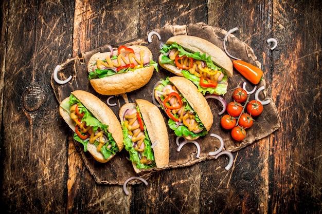 Straatvoedsel. hotdogs met kruiden, groenten en hete mosterd op houten tafel.