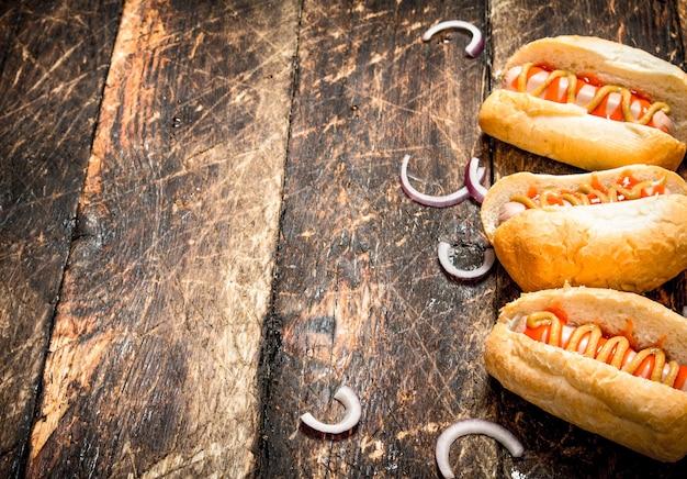Straatvoedsel. hotdogs met mosterd en tomatensaus op houten tafel.