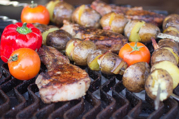 Straatvoedsel: rode tomaten, vlees en aardappelen op de grill. detailopname