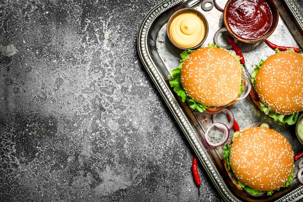 Straatvoedsel verse hamburgers met groenten en sauzen op een stalen bakje op een rustieke achtergrond