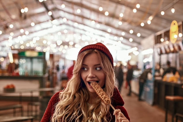 Straatvoedselcultuur. jonge blonde vrouw in rode dop en ecobontjas die veganistische worst eet in deeg op straatmarkt.
