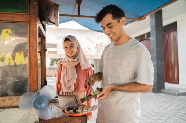 Straatvoedselverkoper met wandelende kraam met indonesische kipsaté die kookt op een hete houtskoolgrill