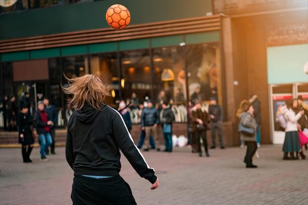 Straatvoetbal freestyle artiest. een jonge man doet voetbaltrucs op straat