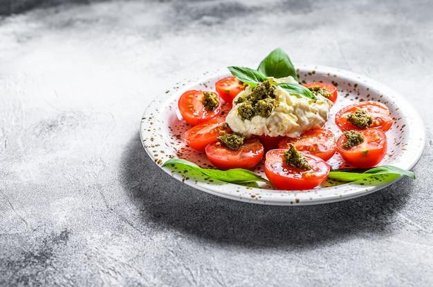 Stracciatella (mozzarella buffels) op kleine plaat geserveerd met verse tomaten en basilicum. grijze achtergrond. ruimte voor tekst
