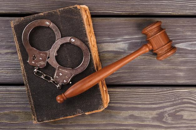 Straf- en arrestatieconcept. houten hamer met handboeien en oud versleten boek. oude bureauachtergrond.