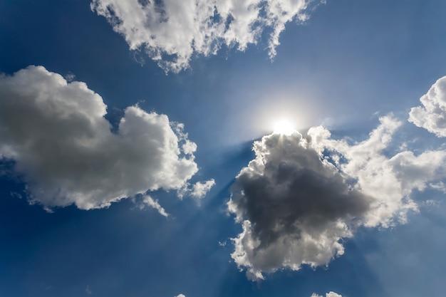 Stralen van de zon schijnt door witte gezwollen wolken en blauwe hemel