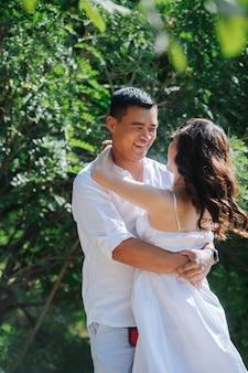 Stralende aziatische man verliefd zijn vrouw in handen houden en haar spinnen. in een struik in een park, weg van de ogen van anderen. elkaar aankijken, elkaar vasthouden.