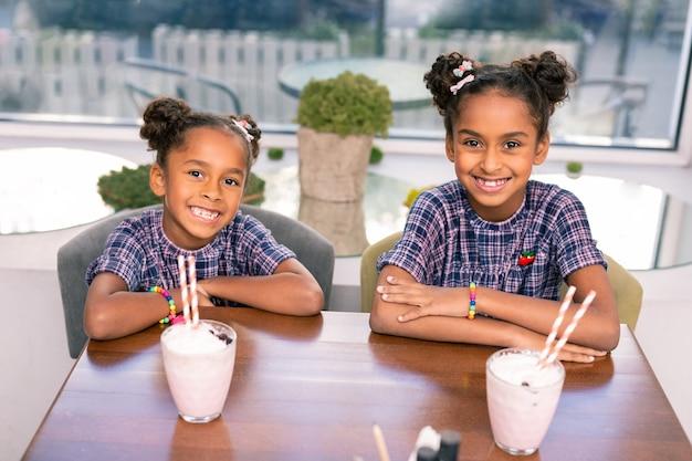 Stralende broers en zussen. twee schattige stralende broers en zussen voelen zich buitengewoon gelukkig in cafetaria drinken melkcocktail