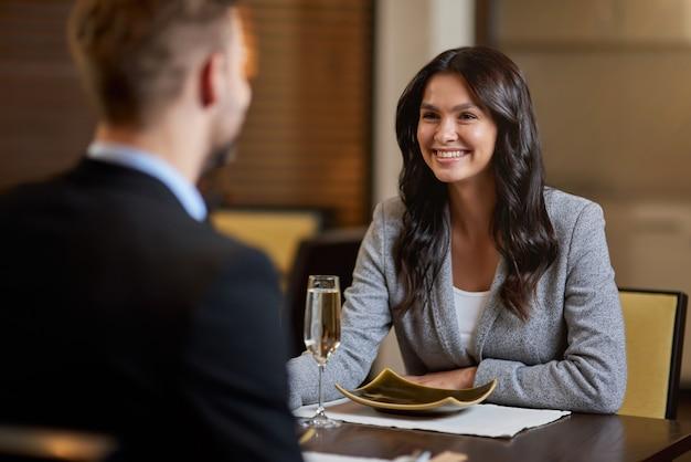 Stralende brunette vrouw die lacht terwijl ze naar haar partner kijkt die tegenover haar aan de tafel van het restaurant zit