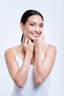Stralende glimlach. schitterende donkerharige jonge vrouw in een wit mouwloos onderhemd poseren tegen een witte muur terwijl ze lacht