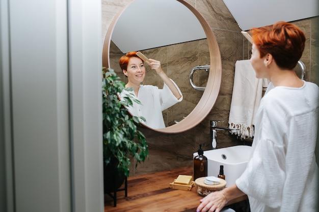 Stralende kortharige volwassen vrouw haar haren kammen met een houten kam. ze staat voor de spiegel in een badkamer, reflectie in een focus.