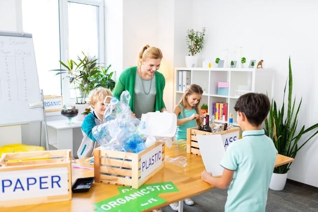 Stralende leraar. stralende blonde lerares voelt zich goed bij het zien van haar schattige leerlingen die afval sorteren