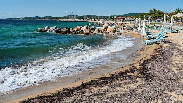 Strand aan de egeïsche zeekust met gesloten parasols en ligbedden, rotsen aan het water, dijkstraat, zeehaven en groene heuvels in de verte in nikiti, griekenland