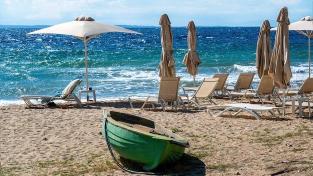 Strand aan de egeïsche zeekust met parasols en ligbedden, gestrande boot gemaakt van groen gekleurd metaal in nikiti, griekenland