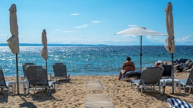 Strand aan de egeïsche zeekust met parasols en ligbedden, rustend paar, rotsen in de buurt van het water in nikiti, griekenland