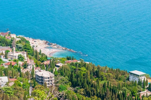 Strand aan zee, turkooisblauw water, uitzicht van bovenaf vanaf de bergen naar de stad simeiz, yalta, de krim