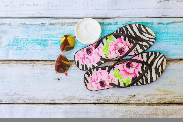 Strand accessoires. zomerschoenen en handdoek met zonnebril en zonnebrandolie op een houten ondergrond