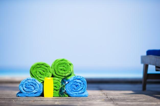 Strand en de zomer het concept van vakantietoebehoren - close-up van kleurrijke handdoeken, zwembril en sunblock