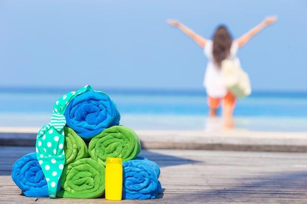 Strand en de zomertoebehorenconcept - kleurrijke handdoeken, zwempak en sunsblock mooie vrouw als achtergrond