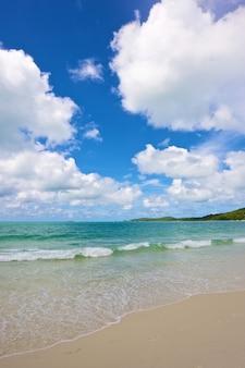 Strand en tropische zee onder de heldere blauwe hemel op zomerdag