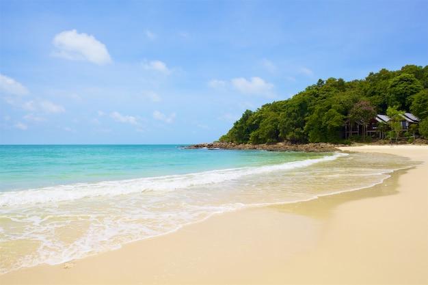 Strand en tropische zee onder de heldere blauwe hemel