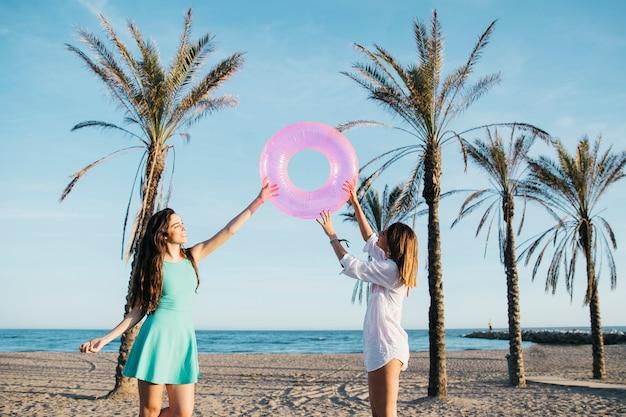 Strand en zomer concept met vrouwen spelen met opblaasbare ring