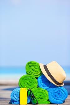 Strand en zomer vakantie accessoires concept van closeofup van kleurrijke handdoeken, hoed en zonnebrandcrème