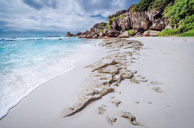 Strand grand anse op het eiland la digue, seychellen. wit zand en unieke granieten rotsformatie op de achtergrond.