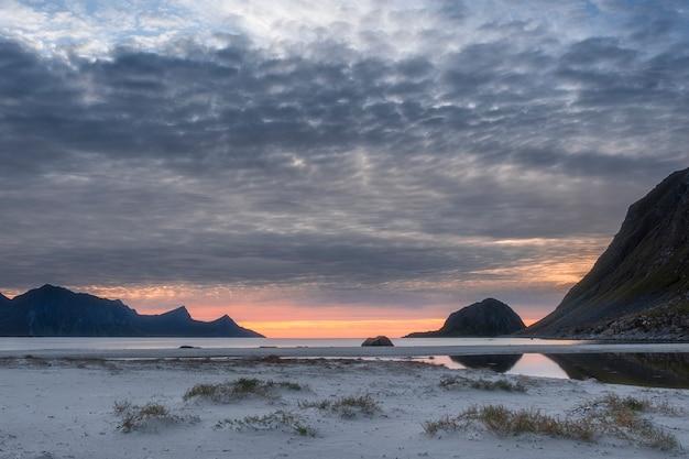 Strand haukland met wit zand, en bergen de lofoten-eilanden in polair noorwegen na zonsondergang