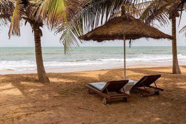 Strand in gambia met rieten parasols, palmen en strandstoelen met de zee op de achtergrond