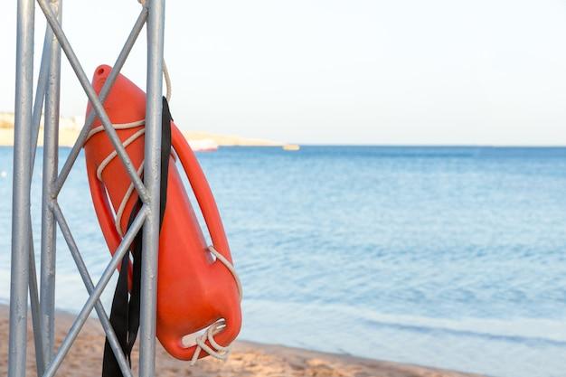 Strand levensreddend. badmeester toren met oranje boei op het strand.