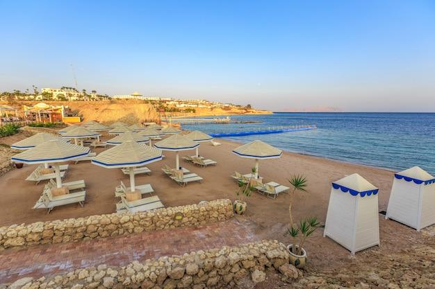 Strand met ligstoelen en parasol tijdens zonsondergang