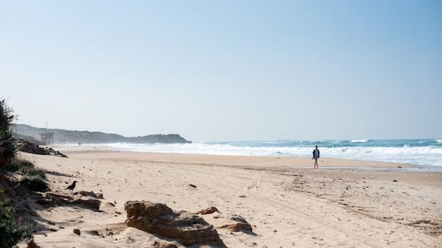 Strand met mensen erop omgeven door de zee en heuvels bedekt met groen onder zonlicht