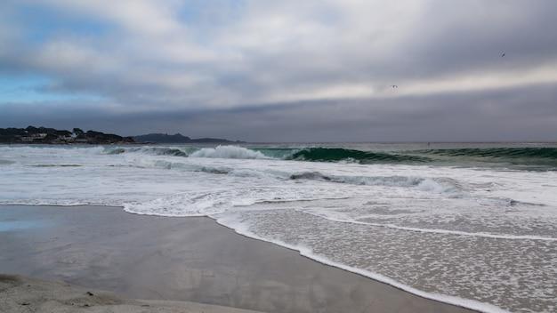 Strand met oceaangolven in een stormachtige zonsondergang