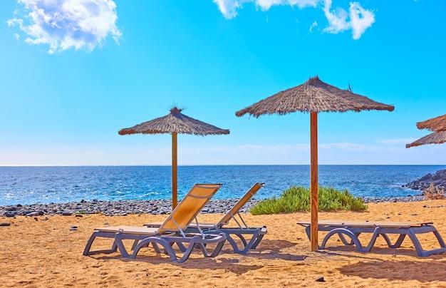 Strand met parasols en ligbedden aan zee op zonnige zomerdag