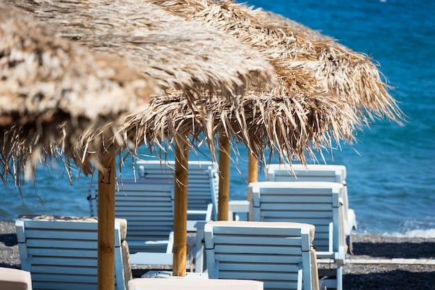 Strand met parasols en ligstoelen aan zee in santorini