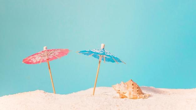 Strand met rode en blauwe parasols