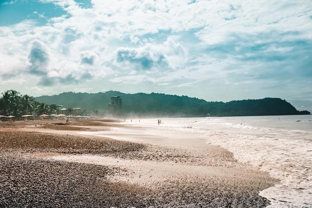 Strand met stoelen en parasols met de jungle en bergen. jaco, costa rica