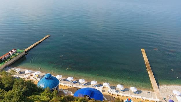 Strand met toeristen die op een zonnige ochtend in de zee ontspannen