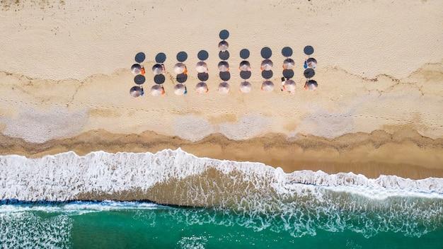 Strand met veel parasols en ligbedden, golven van de egeïsche zee