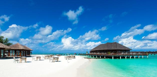 Strand met wit zand, turkoois oceaanwater en blauwe hemel met wolken in zonnige dag. natuurlijke achtergrond voor zomervakantie. panoramisch zicht.