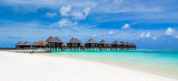 Strand met wit zand, turkoois oceaanwater en blauwe hemel met wolken in zonnige dag.