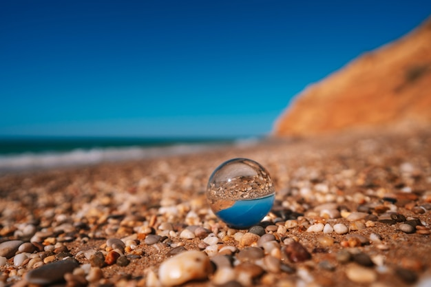 Strand met zee gefotografeerd door een kristallen bol in focus