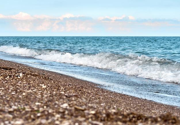 Strand met zee kiezelstenen en schelpen op een achtergrond van de zeegolf.