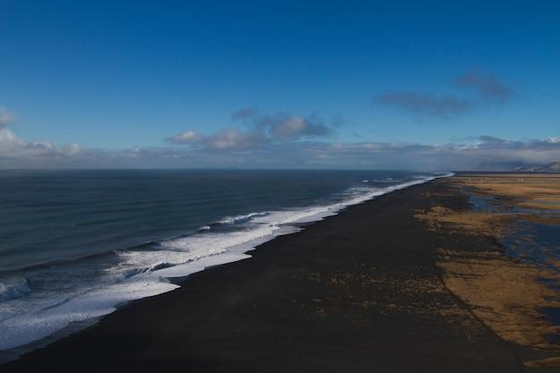 Strand omgeven door de zee met heuvels onder een bewolkte hemel in ijsland
