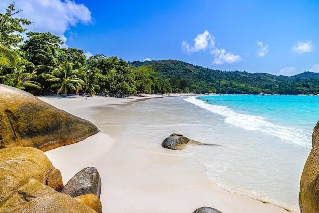 Strand omgeven door de zee rotsen en groen onder het zonlicht in praslin op de seychellen