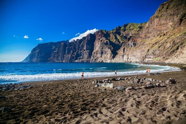 Strand playa de los guios in los gigantes met vier rennende mannen, tenerife, canarische eilanden, spanje