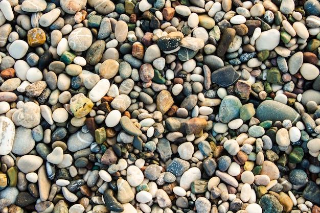 Strand stenen kiezels. de textuur van kleine stenen en zand. kan gebruikt worden als textuur achtergrond