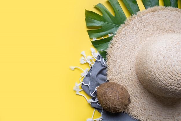 Strand stro zonnehoed, kokosnoten, zeeschelp en monsterabladeren. zomervakantie met accessoires. bovenaanzicht.