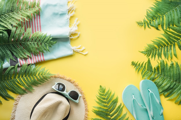 Strand stro zonnehoed, zonnebril, slippers op geel